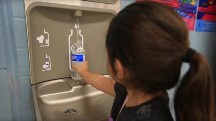 water bottle filling school latino girl