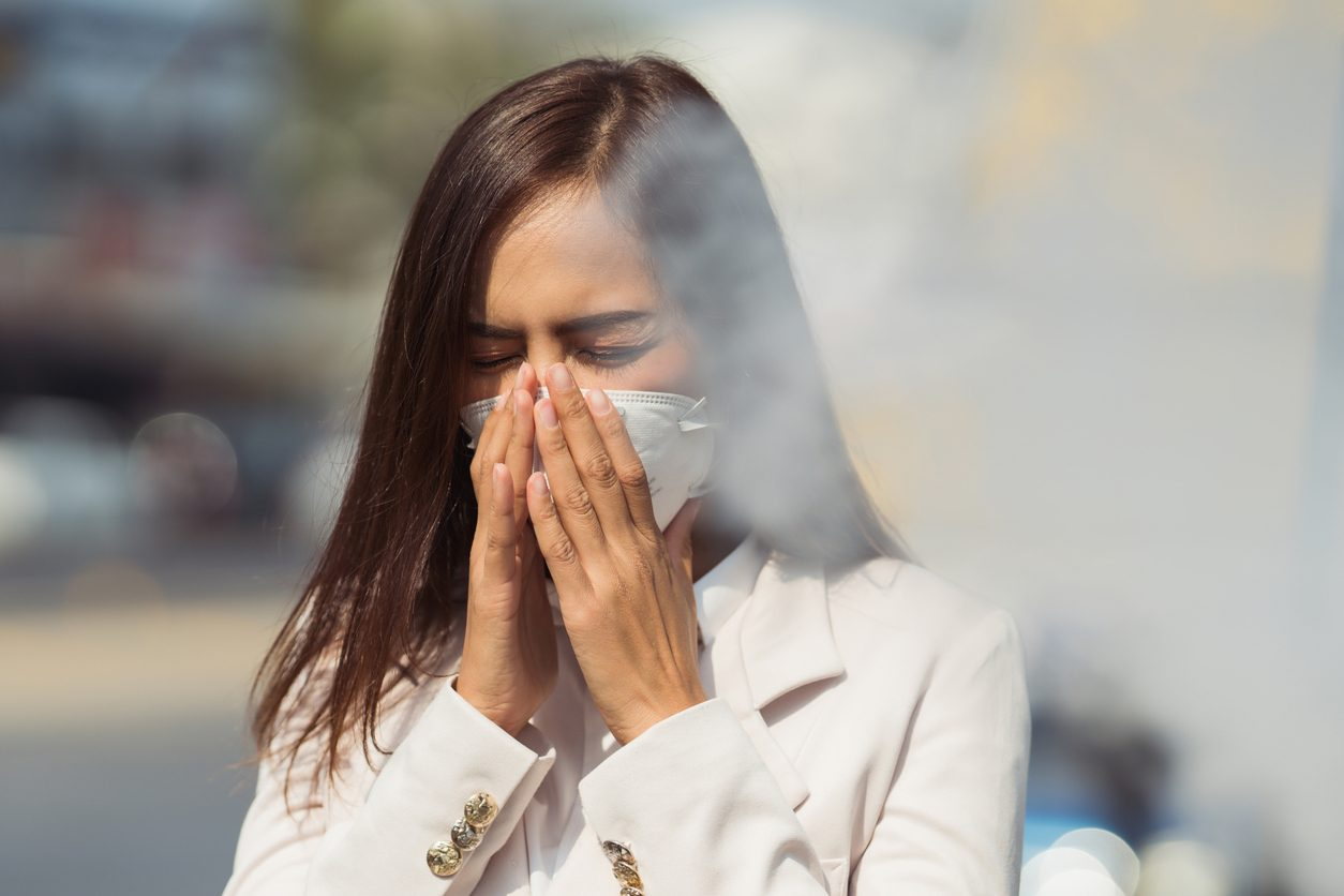 Woman coughing due to smoke smoke-free policy for indoor air mil gracias